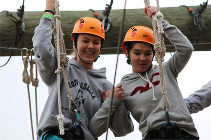 Students in hardhats doing the high-ropes challenge